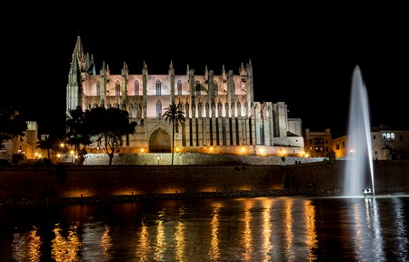 Cathedral of Palma de Mallorca at night with its illuminated fountain and Lights reflecting on the pool - Balearic Islands, Spain.