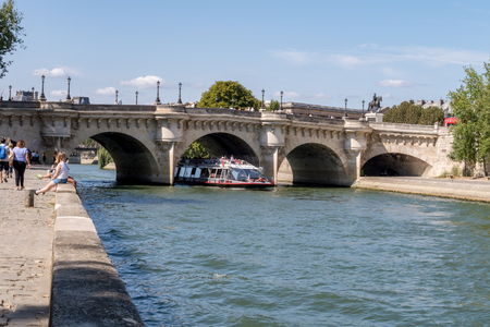 Boat traffic under the Pont Neuf - Paris, France. Pont Neuf is the oldest standing bridge across the river Seine. Stock fotó