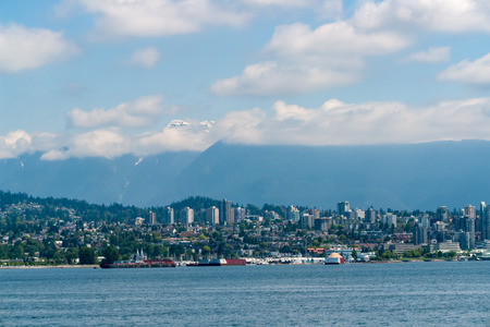 Vancouver with city skyline and snow mountains in background - Vancouver, British Columbia, Canada.