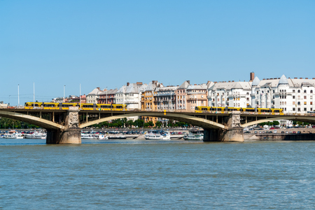 Margaret Bridge in Budapest with Two yellow modern Tramways and typical buildings in background - Budapest, Hungary Banco de Imagens