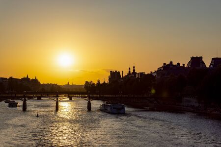 Sunset over Seine river and Pont des arts with palais royal and musee dorsay in background - Paris, France