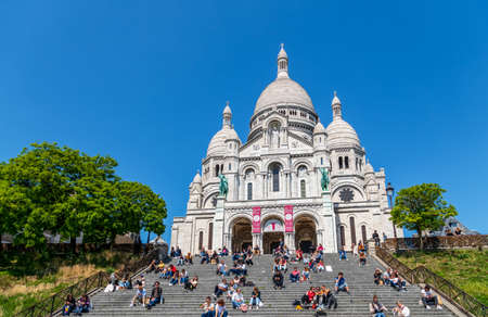 Paris, France - May 15 2020: Parisians at lunch time on Montmartre stairs with Sacre-Coeur basilica in background during Covid-19 epidemic in Paris Editorial