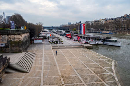 Paris, France - March 17 2020: Coronavirus Lockdown in Paris. Lonely jogger on normaly crowded Seine River riverbank