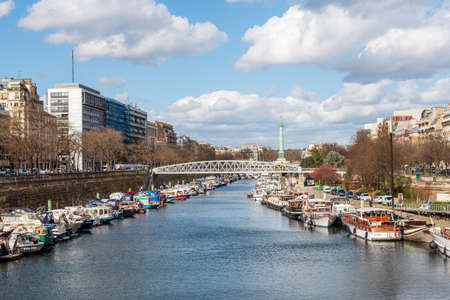 Paris, France - March 12 2020: Boats docked at Arsenal Port on Canal Saint Martin with Bastille July column in background Banco de Imagens - 147926137