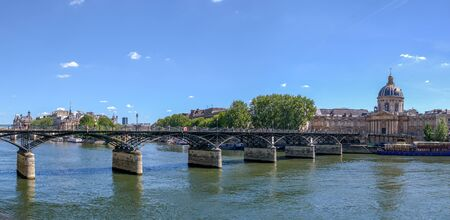 People walking on Pont des Arts bridge on the Seine river with Institut de France in background - Paris