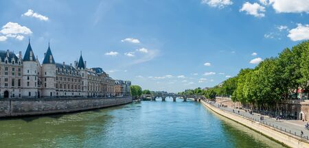 Panoramic view of Seine river with conciergerie palace, pont neuf and Parisians walking on the embankment - Paris, France