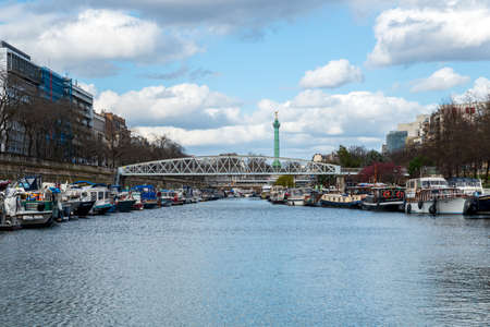 Paris, France - March 12 2020: Boats docked at Arsenal Port on Canal Saint Martin with Bastille July column in background