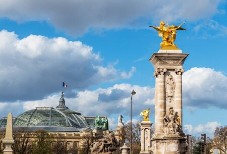 Golden statues of Pont Alexandre III bridge with Grand Palais and French flag waving on top of the building - Paris, France Imagens
