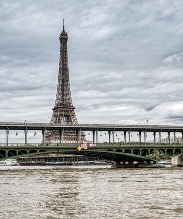Eiffel Tower on a cloudy day with Bir-hakeim bridge in foreground - Paris, France