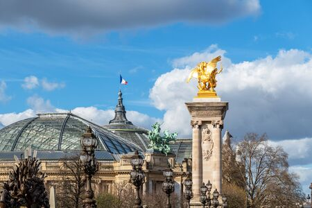 Golden statue and lanterns of Pont Alexandre III bridge with Grand Palais and French flag waving on top of the building - Paris, France Imagens