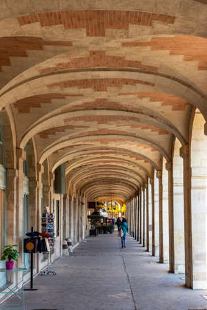 Paris, France - November 21 2019: People walking in shopping arcade at the Place des Vosges.