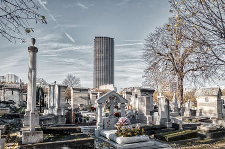 Paris, France - November 22 2019: Montparnasse Cemetery in autumn with montparnasse tower in background Editorial