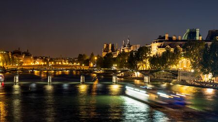 Nightfall over Seine river and illuminated Pont des arts with palais royal and musee d'orsay in background - Paris, France Imagens