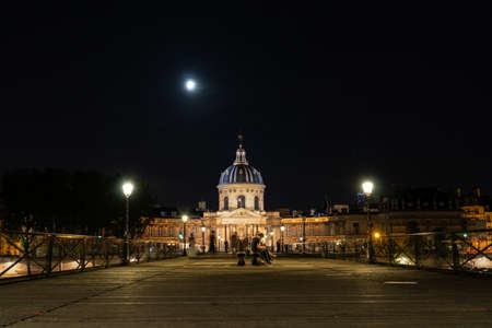 Paris, France - August 08 2019: Institut de France and people walking on Pont des Arts at night - Paris, France.
