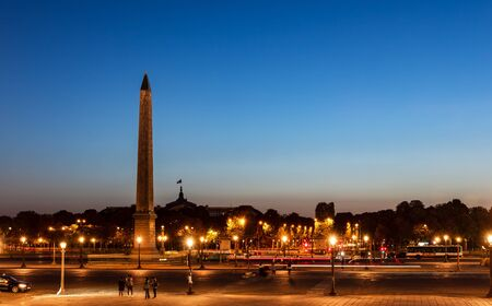 Traffic on Place de la Concorde at night with Obelisk of Luxor and Grand Palais in background - Paris, France