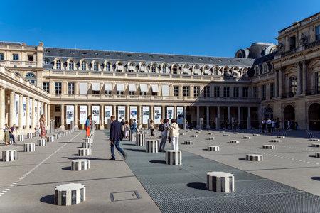 Paris, France - September 02 2019: People walking, posing and photographing between Buren columns (Colonnes de Buren - Les Deux Plateaux) in Cour d'Honneur at Palais Royal.