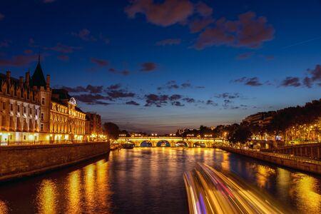 Illuminated Conciergerie and Pont Neuf bridge at night - Paris, France.