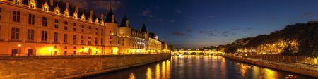 Panorama of Illuminated Conciergerie and Pont Neuf bridge at night - Paris, France.