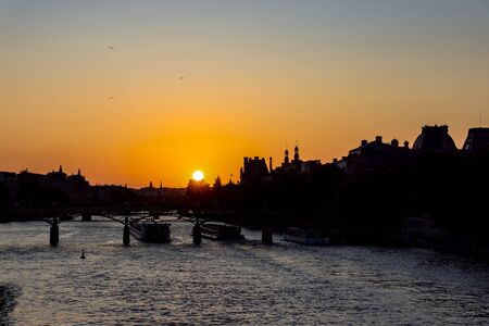 Sunset over Seine river and Pont des arts with palais royal and musee d'orsay in background - Paris, France