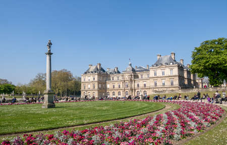 Paris, France - April 11, 2019: People enjoying sunshine in the Luxembourg garden with the Senat in background
