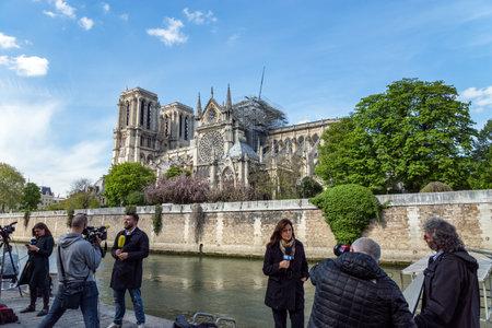 Paris, France - April 17, 2019: Tv reporters in front of Notre Dame de Paris Cathedral after the fire