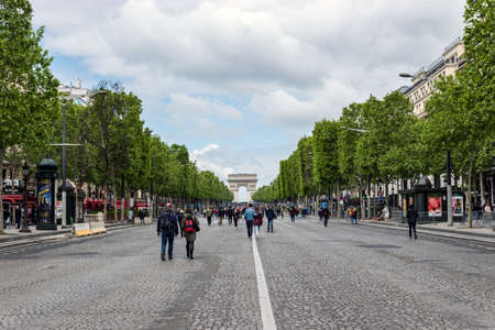 Paris, France - May 5, 2019: People wandering on Champs Elysees avenue with Arc de triomphe in background. The avenue is closed to car traffic on first sunday of the month.