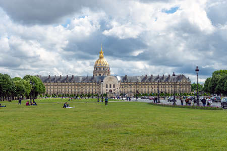 Paris, France - June 10 2019: People walking and resting on avenue des Invalides Grass with Invalide museum in background.