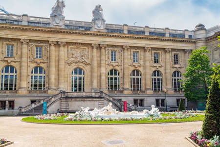 Paris, France - May 12 2020: Grand Palais art exhibitions entrance on square Jean-Perrin with Fontaine Miroir d'eau in foreground