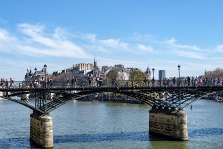 Paris, France - March 30, 2019: People walking on Pont des Arts bridge on the Seine river with barge traffic and Ile de la Cite in background - Paris, France