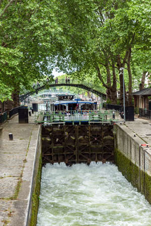 Paris, France - May 26 2019 - Tourist boat wait to enter a Lock of the Canal Saint-Martin