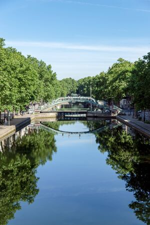 Pedestrian bridge over the Canal Saint-Martin with reflection in the water - Paris, France