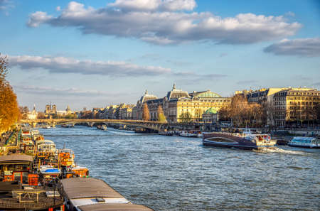 Paris, France - March 26, 2019: Boats traffic on Seine river with Orsay Museum and Passerelle Leopold Sedar Senghor in background - Paris, France Editorial