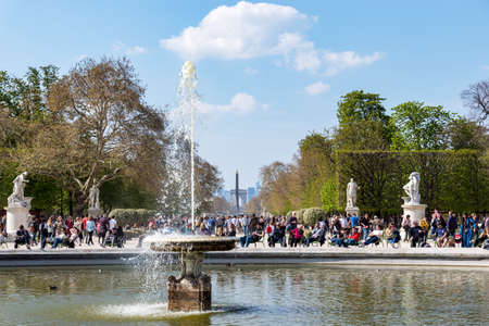 Paris, France - March 31, 2019: People enjoying sunshine in the Jardin des Tuileries in early spring with the Obelisk of Place de la Concorde and the Arc de Triomphe in background