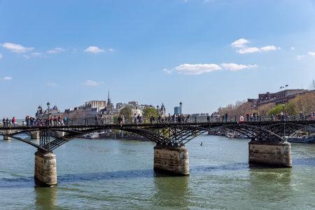 Paris, France - March 31, 2019: People walking on Pont des Arts bridge on the Seine river with Ile de la Cite in background Editorial