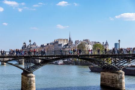 Paris, France - March 31, 2019: People walking on Pont des Arts bridge on the Seine river with barge traffic and Ile de la Cite in background
