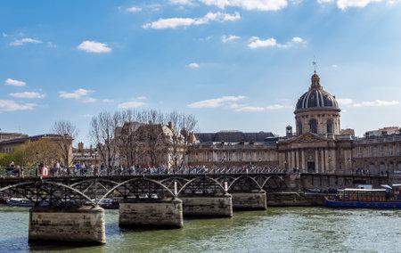 Paris, France - March 31, 2019: People walking on Pont des Arts bridge on the Seine river with France Institute (Institut de France) in background