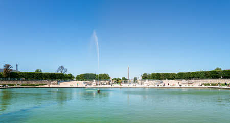 Paris, France - June 01 2020: Panoramic over the Octagonal Basin in the Jardin des Tuileries with the Luxor Obelisk and the Arc de Triomphe in the background