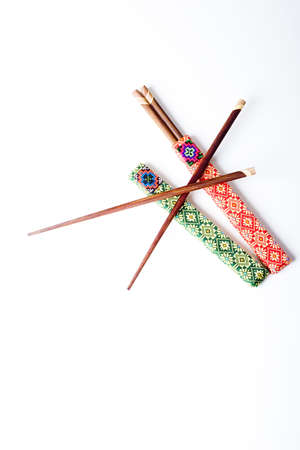 Two pairs of wooden chopsticks in red and green covers isolated on a white background photo