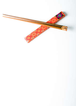 Pair of wooden chopsticks in red cover isolated on a white background