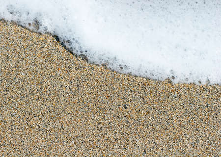 White sea foam on a yellow brown sand grains