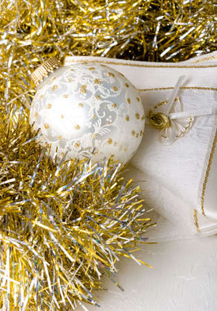 Decoration Christmas New Year silver ornament ball on a shiny golden background with fabric napkin
