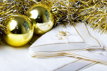 Shiny golden color Christmas New Year decoration ornament balls with textured fabric napkins on a table