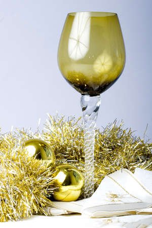 Luxurious expensive tall wine glass on a beautiful Christmas New Year theme decorated table with golden ornament balls
