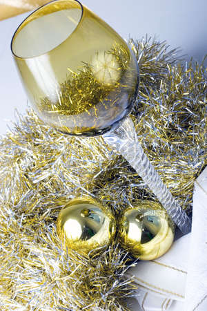 Luxurious expensive tall wine glass on a beautiful Christmas New Year theme decorated table with golden ornament balls view from top
