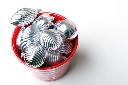 Bunch of Christmas New Year silver shiny decoration ornaments in red basket