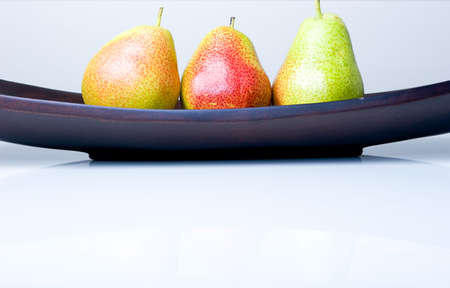 Three delicious fresh colorful pears in a wooden vase