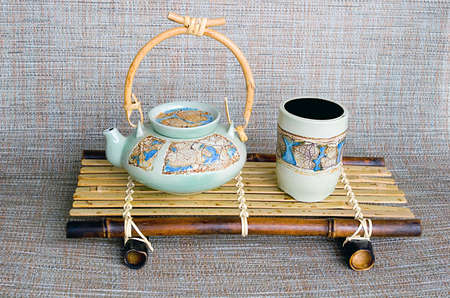 stand teapot: Japanese style ceramic teapot and cup on the bamboo stand