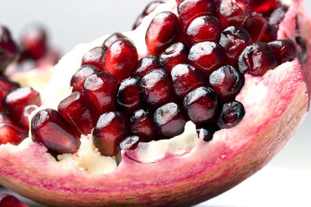 Cut out slice of a fresh ripe pomegranate fruit close up Stok Fotoğraf