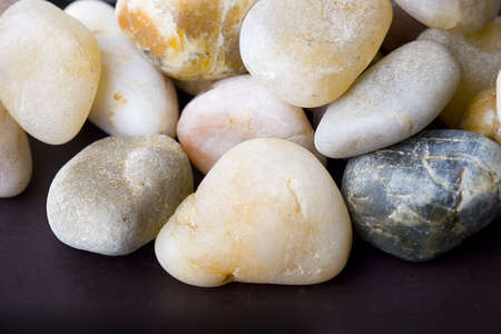Abstract background of small colorful pebble stones over brown close up