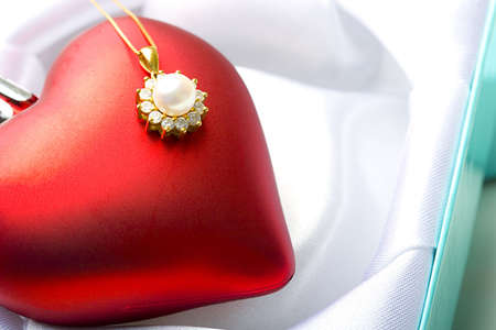 Jewelry pearl pendant Valentine Day gift on a red heart love symbol